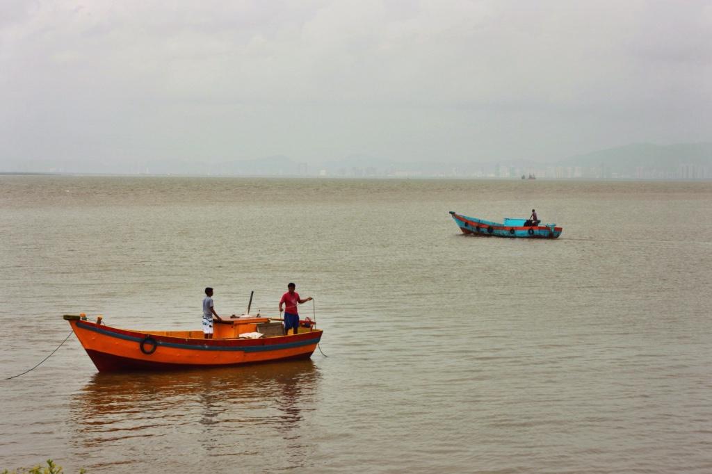 men on boats outside Mumbai, India