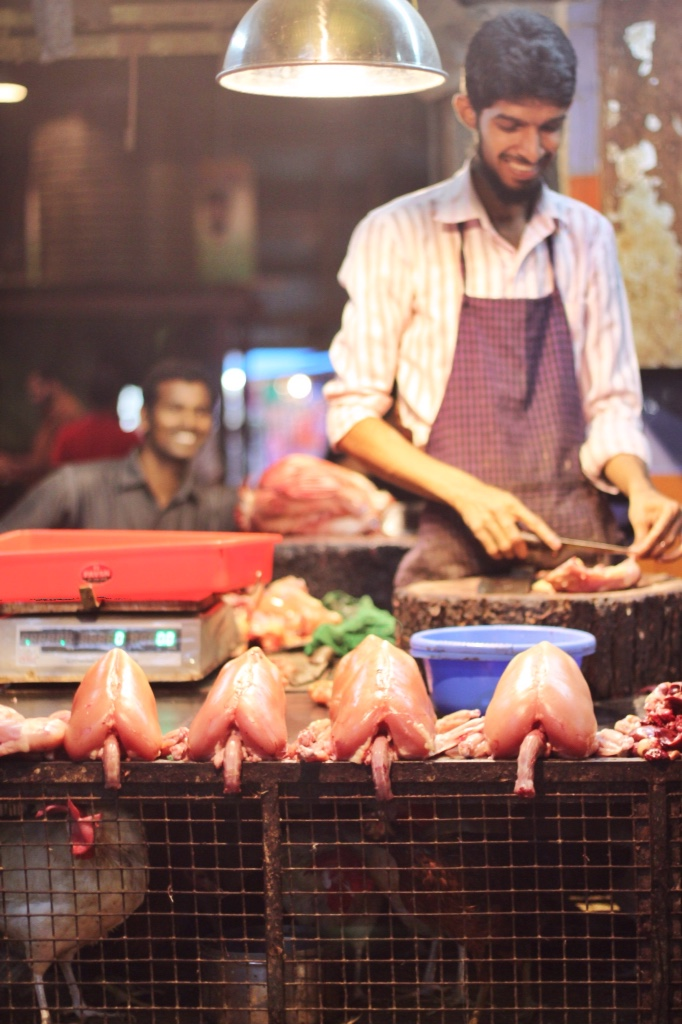 Mumbai market butcher with freshly butchered chickens